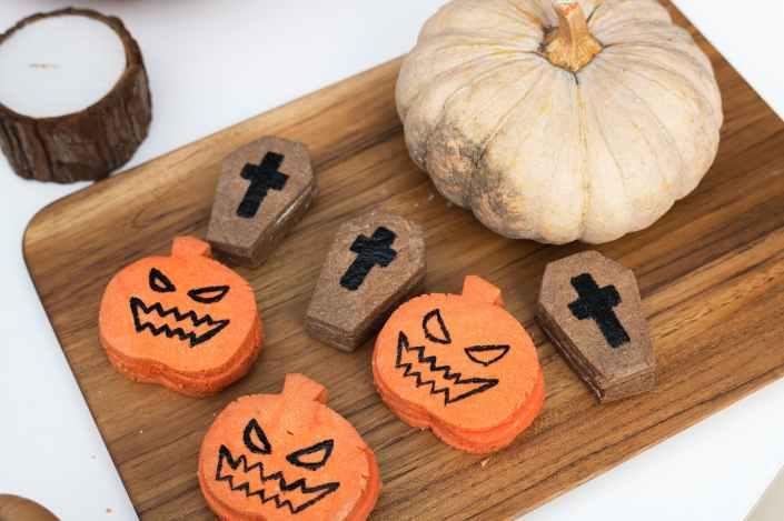 pumpkin jack o lantern and coffin cookies on chopping board
